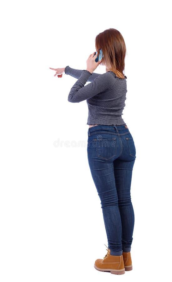Achtermening van het richten van jonge vrouwen die op celtelefoon spreken stock afbeeldingen