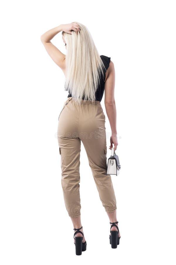 Achtermening van het sexy wachten van de blondevrouw en wat betreft rechtstreeks lang haar stock fotografie
