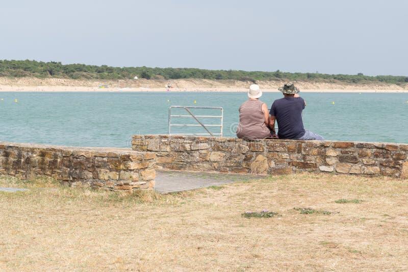 Achtermening van hoger paar die de Atlantische Oceaan in overzees strand in Vendee Frankrijk kijken royalty-vrije stock afbeelding