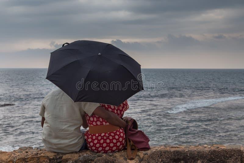 Achtermening van Indische paarzitting door overzees met een paraplu die horizon bekijken royalty-vrije stock foto