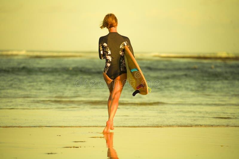 Achtermening van jong aantrekkelijk en sportief surfermeisje in koel zwempak bij de raad van de strand dragende branding in het o stock foto