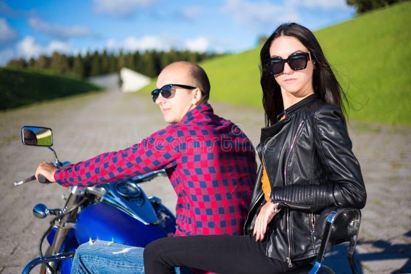 Achtermening van jong mooi paar die op motorfiets berijden stock afbeeldingen