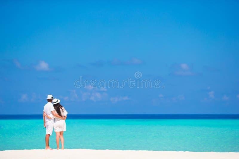 Achtermening van jong paar op wit strand bij de zomer stock foto