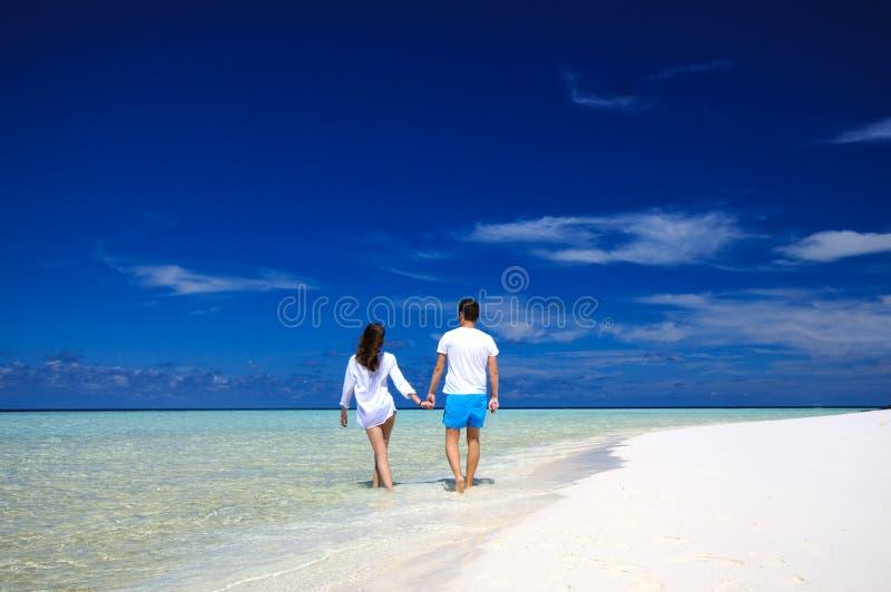 Achtermening van jong paar op wit strand Het concept van de vakantie royalty-vrije stock afbeelding