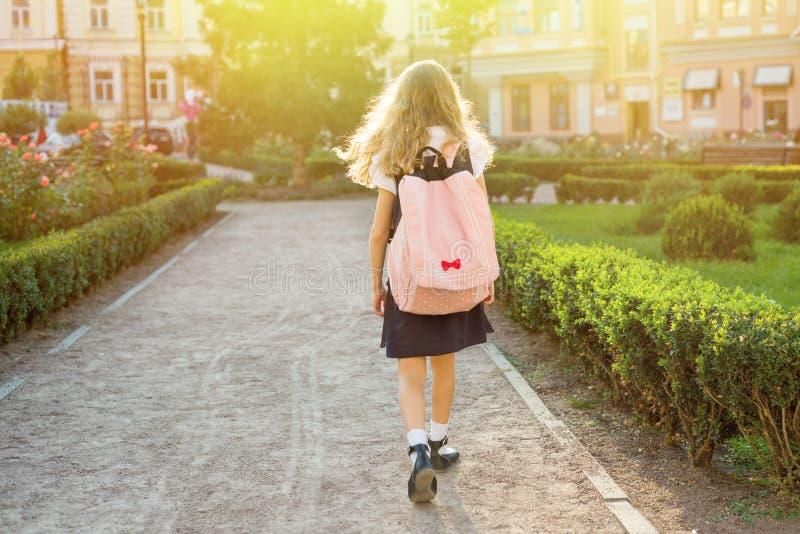 Achtermening van jong schoolmeisje in eenvormig met rugzak die gaan aan royalty-vrije stock afbeeldingen