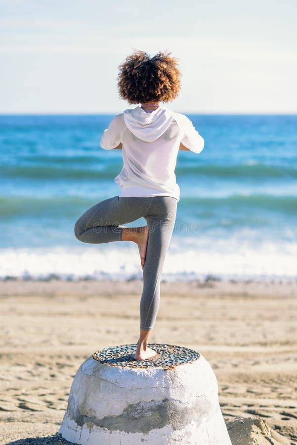 Achtermening van jong zwarte die yoga in het strand doen stock foto's