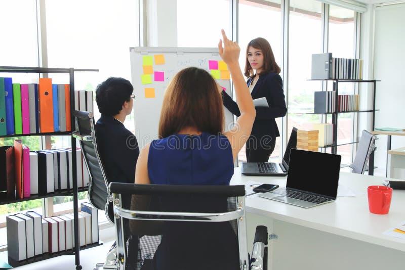 Achtermening van jonge Aziatische vrouw die handen opheffen en een vraag stellen tijdens presentatie in conferentieruimte stock afbeelding