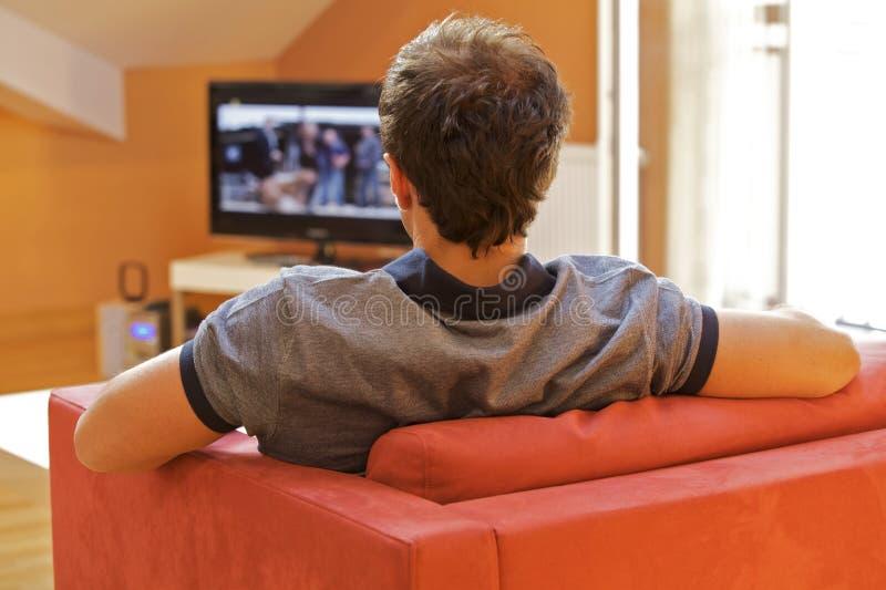 Achtermening van jonge mens het letten op televisie stock foto's