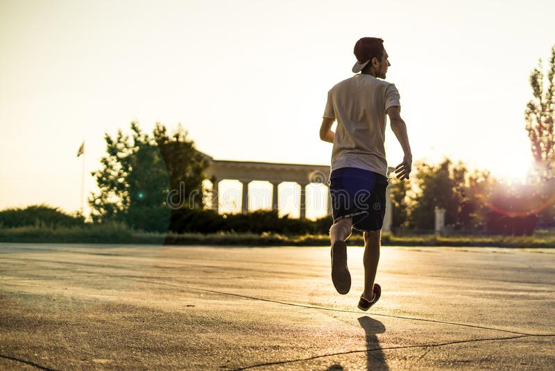 Achtermening van jonge mensenatleet in toevallig silhouet die in de stedelijke stad op een zonsondergang lopen royalty-vrije stock foto