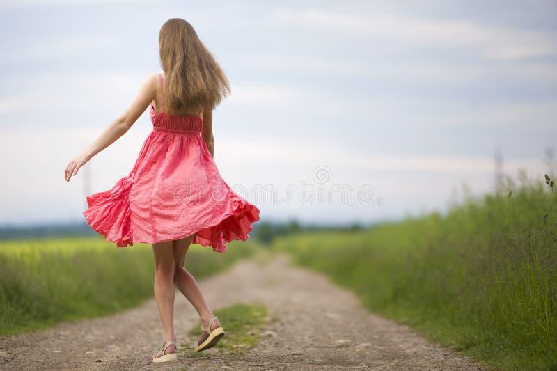 Achtermening van jonge romantische slanke vrouw die in rode kleding met lang haar door grondweg lopen langs groen gebied op zonni royalty-vrije stock foto's