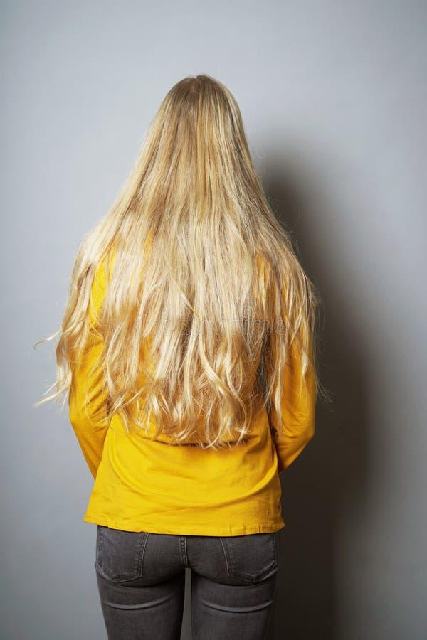 Achtermening van jonge vrouw met lang blond haar royalty-vrije stock afbeelding