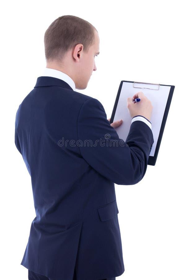 Achtermening van jonge zakenman in kostuum die iets in klem schrijven royalty-vrije stock afbeelding