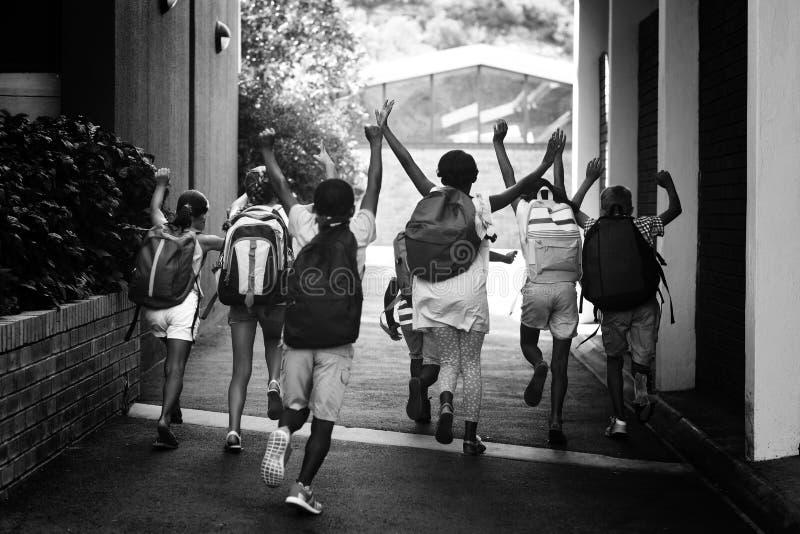 Achtermening van klasgenoten die bij schoolcampus lopen royalty-vrije stock foto's
