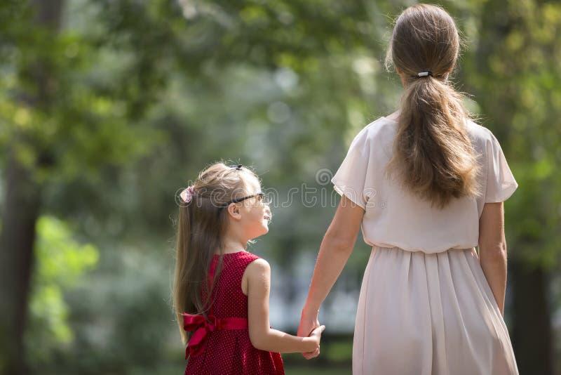 Achtermening van klein blond langharig kindmeisje met slanke sli stock foto