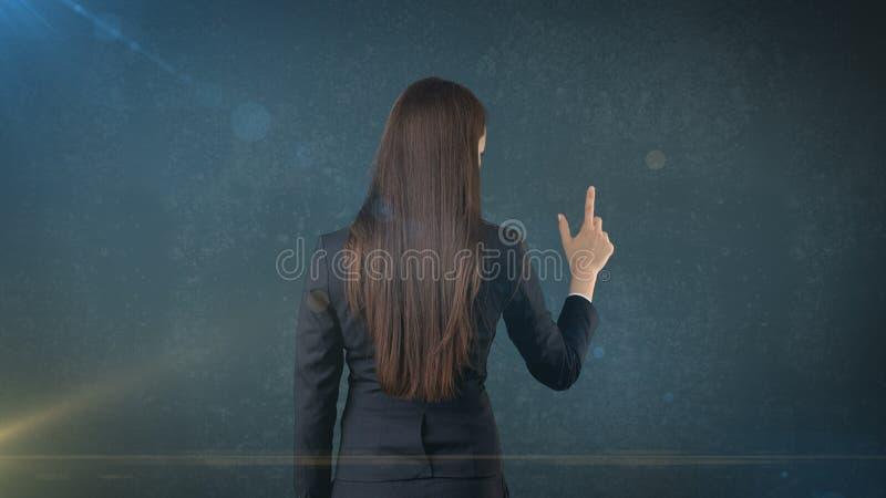 Achtermening van lange donkere haarschoonheid die of op haar rechterkant richten voorstellen stock foto