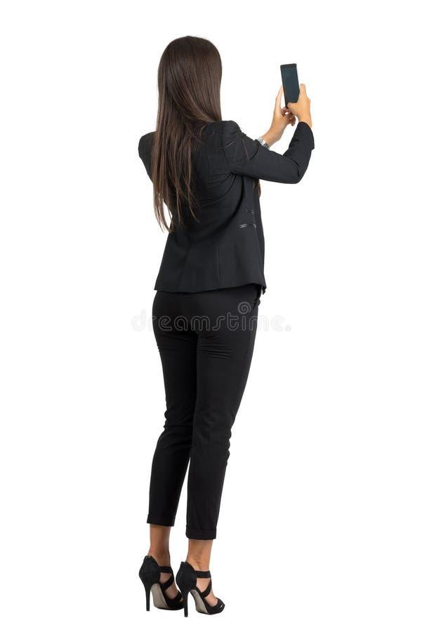 Achtermening van lange haar collectieve vrouw in kostuum die foto met mobiele telefoon nemen royalty-vrije stock foto's