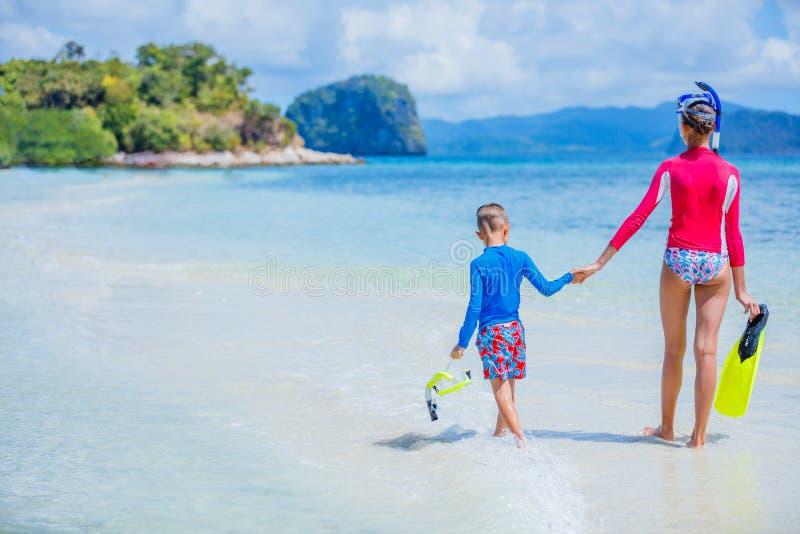 Achtermening van Leuke meisje en jongen die op tropisch strand lopen stock afbeeldingen
