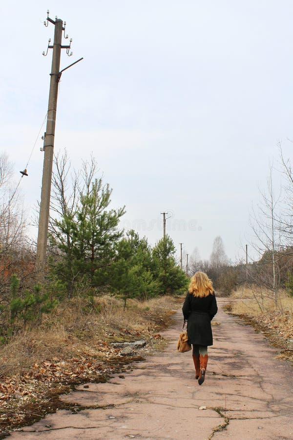 Achtermening van longhair jonge vrouw op de verlaten weg stock afbeelding