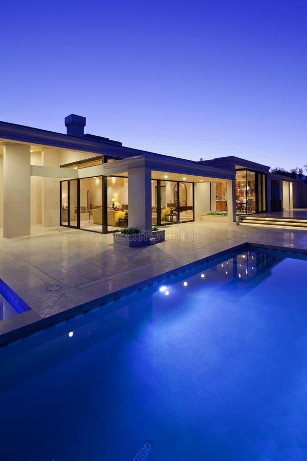 Achtermening van luxevilla bij nacht met zwembad royalty-vrije stock foto's