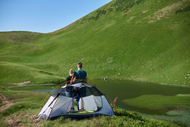 Achtermening van mannetje die het vrouwelijke dichtbijgelegen het kamperen bekijken op meer bergen koesteren stock afbeeldingen