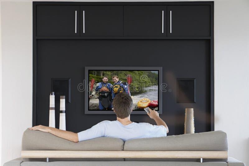 Achtermening van medio-volwassen mensen veranderende kanalen met televisieafstandsbediening in woonkamer royalty-vrije stock afbeeldingen
