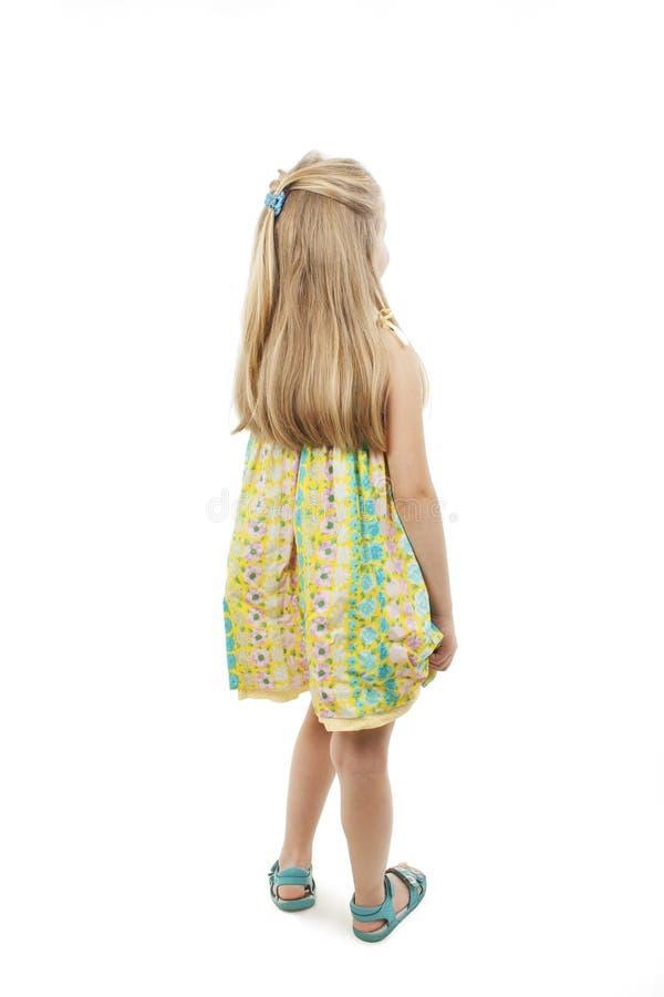 Achtermening van meisje in bloemenkleding die muur bekijken royalty-vrije stock foto's