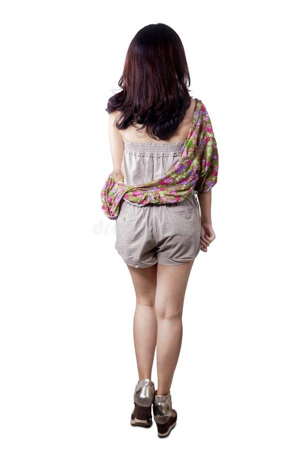 Achtermening van meisje het lopen in studio stock foto's