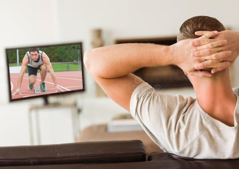 Achtermening van mensenzitting op bank het letten op sportkanaal op TV in woonkamer royalty-vrije stock fotografie