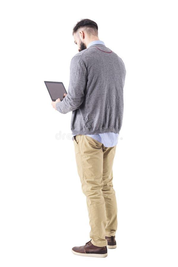 Achtermening van modieuze gebaarde zakenman die de computer van het tabletstootkussen met behulp van royalty-vrije stock afbeeldingen