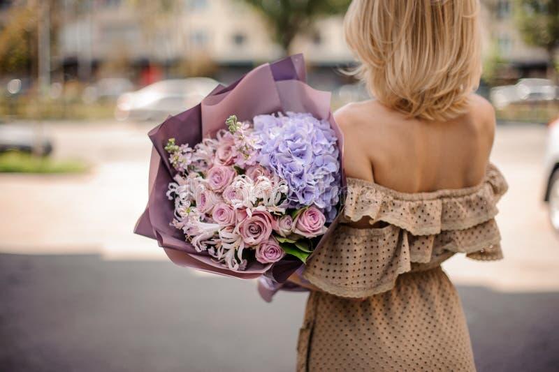 Achtermening van mooie blondevrouw die in beige kleding een ROM houden royalty-vrije stock fotografie
