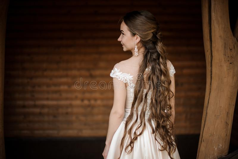 Achtermening van mooie en glimlachende bruid in lange huwelijkskleding met een lang kapsel stock afbeeldingen