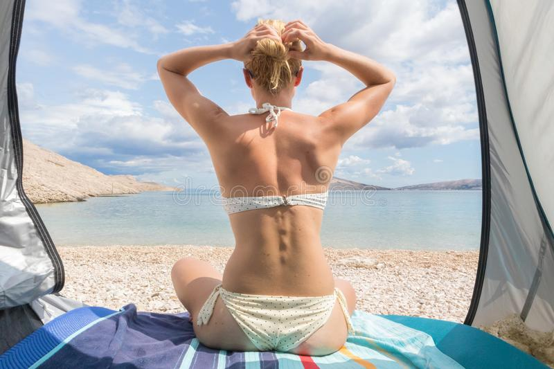 Achtermening van mooie jonge Kaukasische vrouw die de zomer van zon op Mediterraan die strand genieten tegen hitte en zonnebrand  stock fotografie