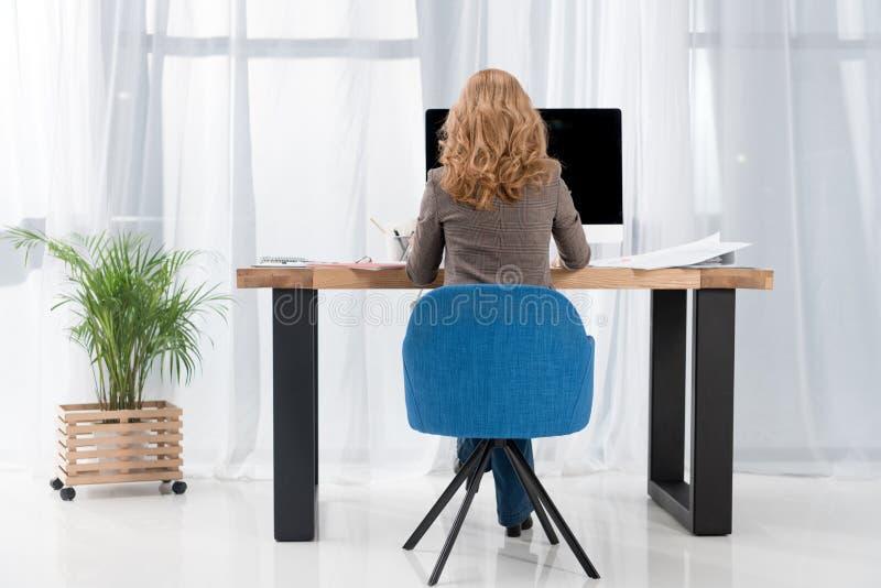 achtermening van onderneemster die bij werkplaats met het computerscherm werken stock fotografie