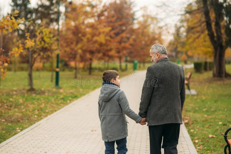 Achtermening van opa en kleinzoon in park Kinderjaren De herfst stock foto's