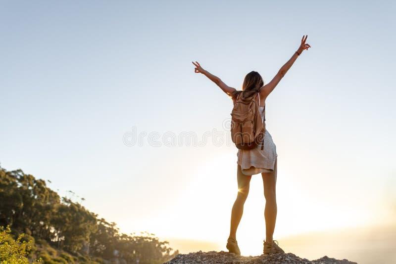 Achtermening van opgewekte jonge vrouw met rugzak die zich op de bovenkant van heuvel met haar uitgestrekte wapens bevinden Vrouw royalty-vrije stock afbeeldingen