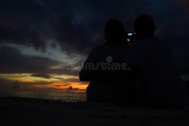 Achtermening van paar die foto op het strand met een mooie zonsondergang op achtergrond doen royalty-vrije stock afbeeldingen