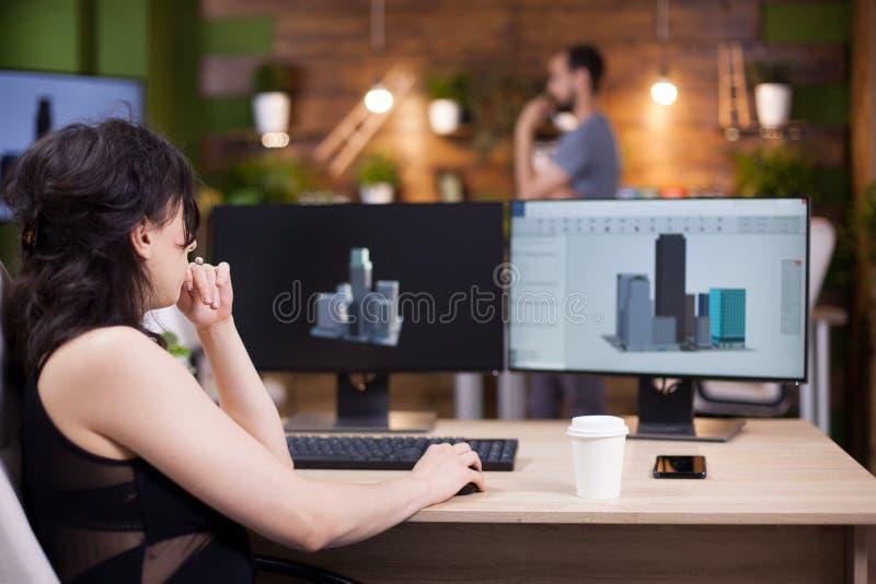 Achtermening van projectleider die aan haar computer werken stock afbeelding
