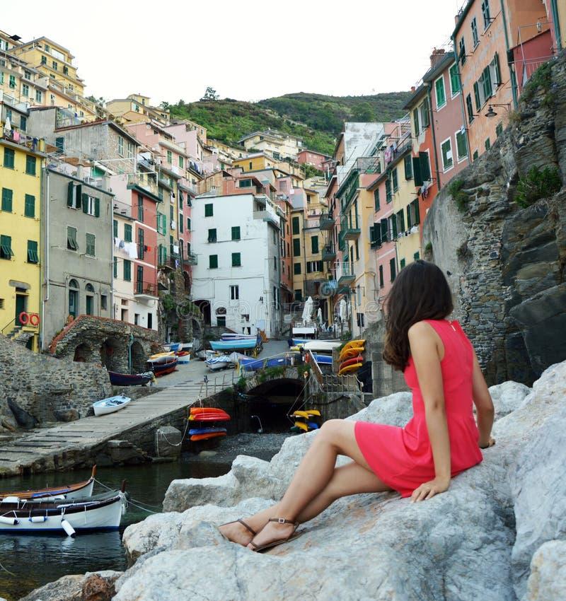 Achtermening van rode geklede meisjeszitting op de stenen zoals een meermin die landschap van Italiaanse Riviera, Riomaggiore, Ci royalty-vrije stock afbeeldingen