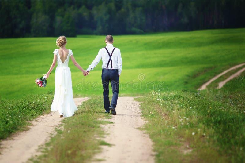 Achtermening van romantisch paar van bruid en bruidegom die hand in hand op landelijke weg lopen royalty-vrije stock afbeeldingen