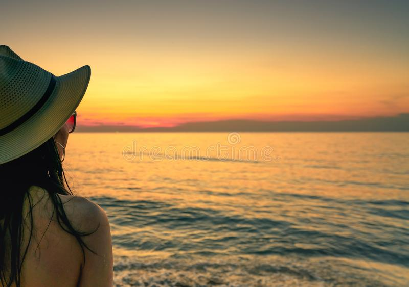 Achtermening van sexy vrouw het letten op zonsondergang bij het strand De zonnebril en het strohoed van de vrouwenslijtage het on royalty-vrije stock afbeeldingen