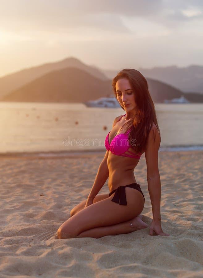 Achtermening van slanke donkerbruine jonge vrouw in bikinizitting op zandig strand stock fotografie