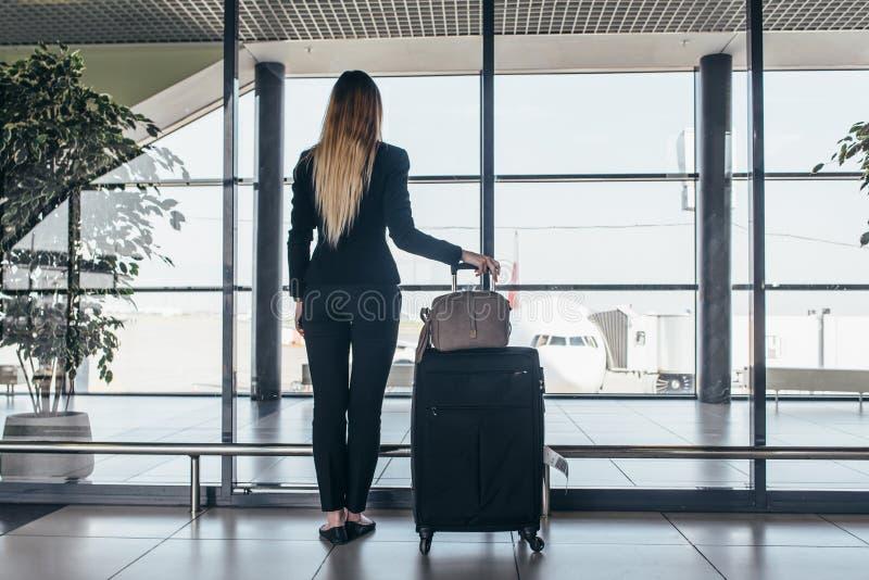 Achtermening van slanke jonge vrouwelijke reiziger status in zware koffers die van de luchthaven de eindholding door het venster  royalty-vrije stock foto