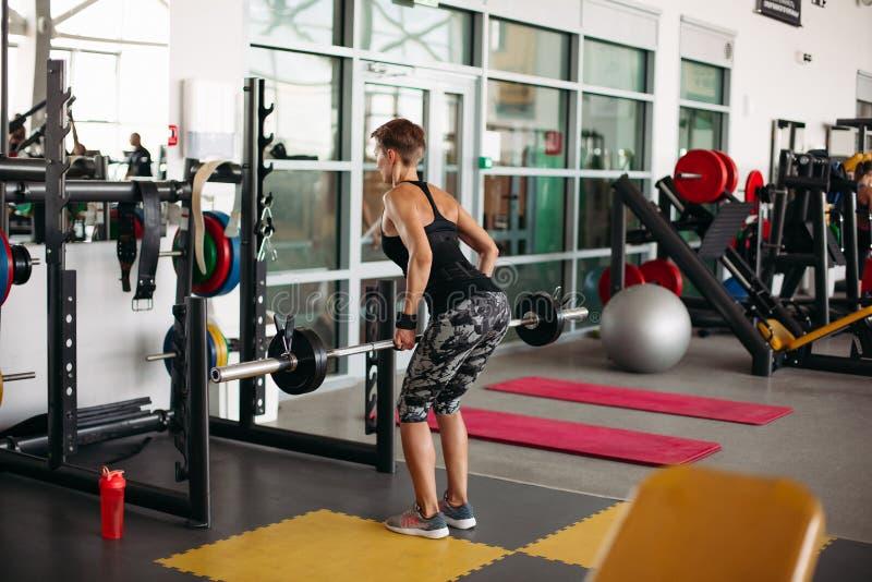 Achtermening van sportieve vrouw die oefeningen met barbell doen stock fotografie