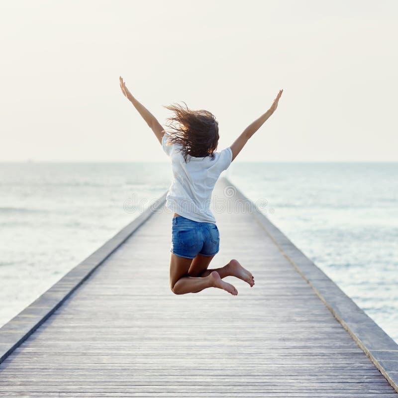 Achtermening van springend meisje op de pijler royalty-vrije stock foto