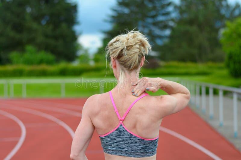 Achtermening van sprinter die haar eigen hals masseren stock afbeeldingen