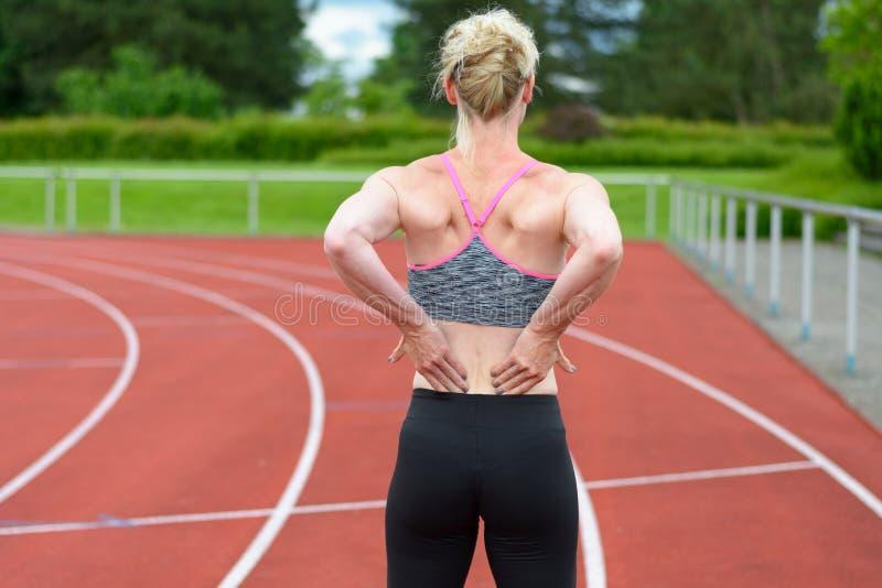 Achtermening van sprinter die haar terug masseren  stock fotografie