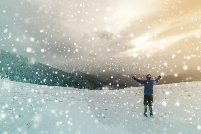 Achtermening van toeristenwandelaar in warme kleding met rugzak die zich met opgeheven die wapens op opheldering bevinden met sne stock foto's
