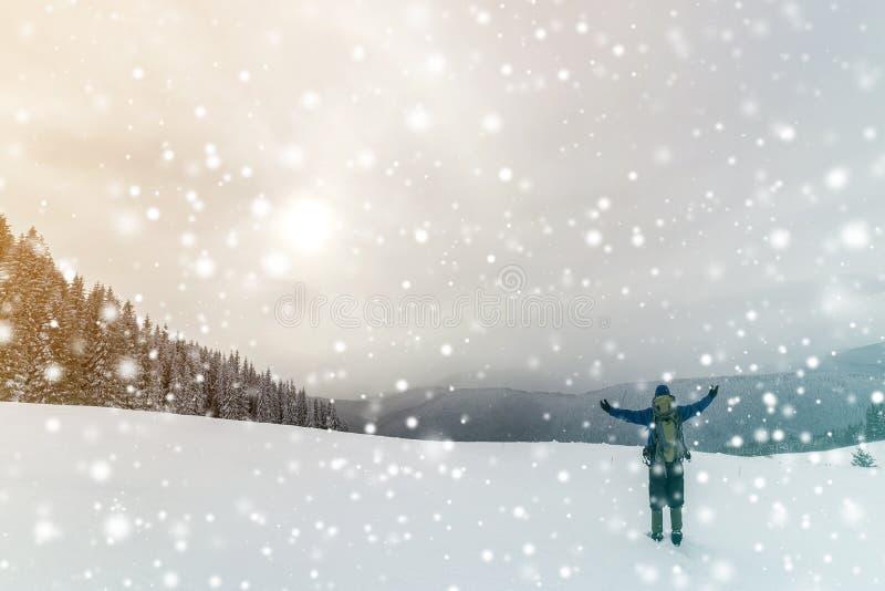 Achtermening van toeristenwandelaar in warme kleding met rugzak die zich met opgeheven wapens op opheldering bevindt die met snee royalty-vrije stock fotografie