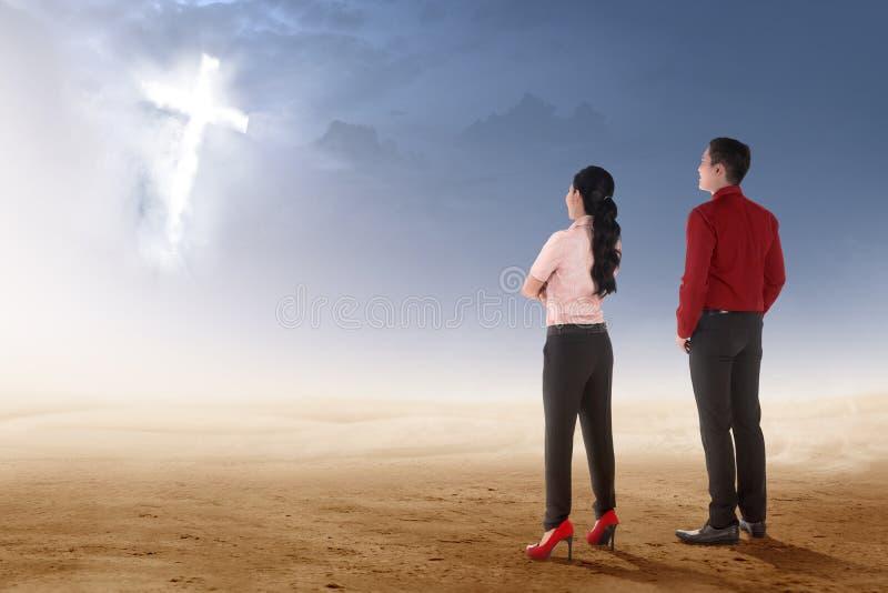 Achtermening van twee Aziatische bedrijfsmensen die zich op woestijn bevinden en gloeiend christelijk kruis bekijken royalty-vrije stock foto's