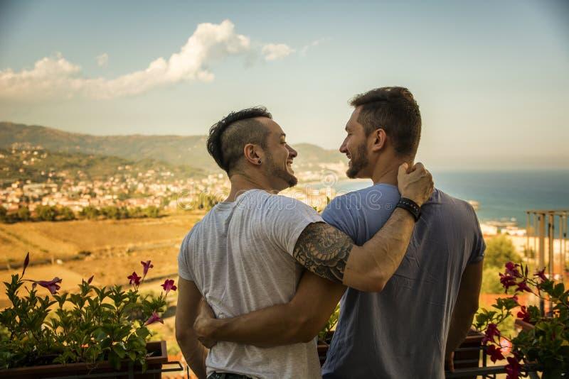 Achtermening van twee homosexuelen het omhelzen stock foto's
